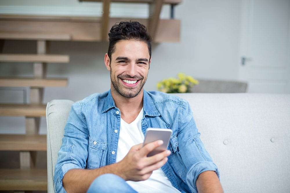 Smiling smart man using smartphone