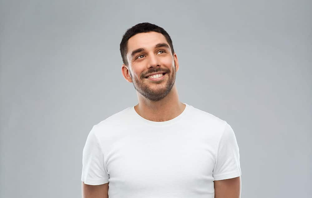 smiling man looking up over gray background