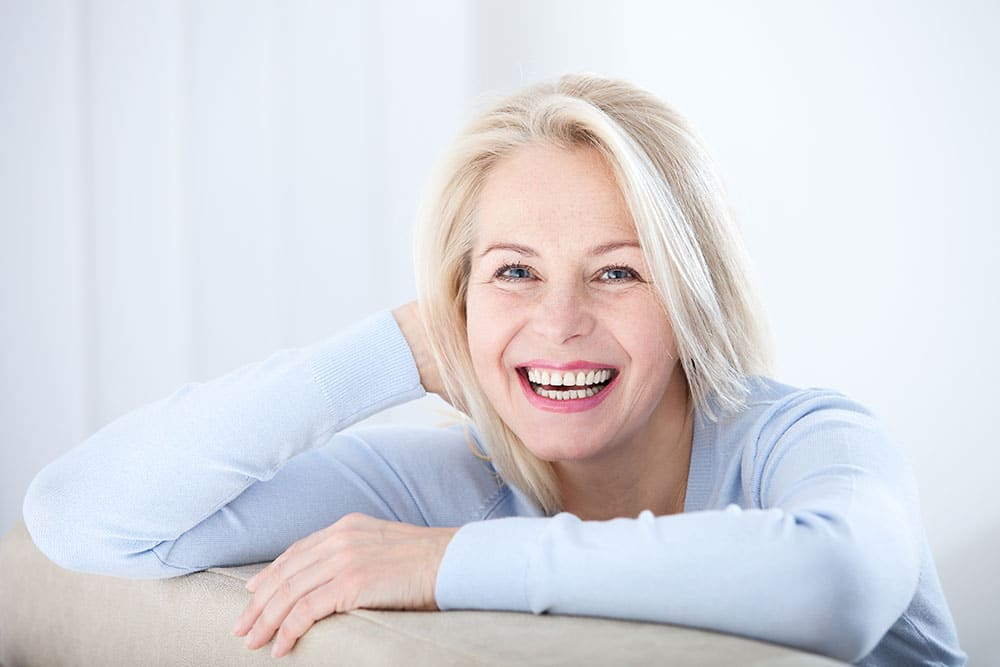 Active beautiful middle-aged woman smiling friendly and looking in camera in living room. Woman's face closeup. Realistic images without retouching with their own imperfections.