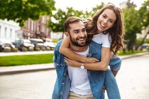 Beautiful young couple in love walking outdoors at the city street, piggyback ride