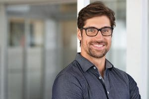 Portrait of handsome businessman standing in modern conference room. Happy young business man in shirt looking at camera with copy space. Portrait of successful smiling guy in office wearing eyeglasses.