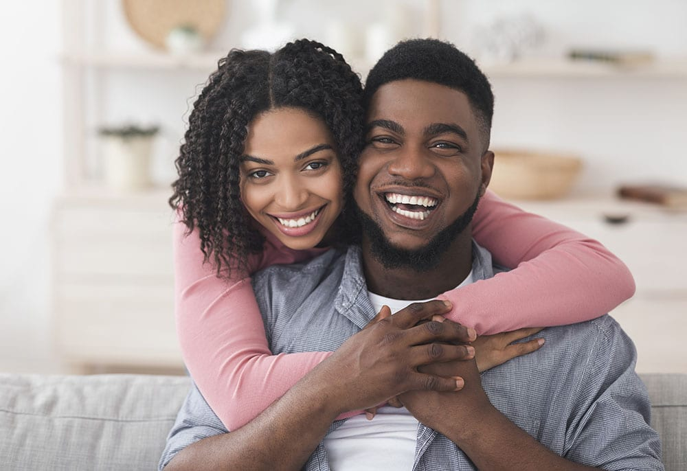 Portrait Of Loving African American Couple Hugging At Home And Looking At Camera, Spending Quarantine Together