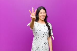 young pretty latin woman smiling and looking friendly, showing number three or third with hand forward, counting down against purple wall