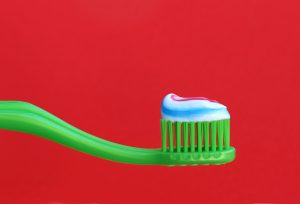 green toothbrush with striped toothpaste in front of a red background